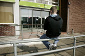 An unemployed young man who has just been released from prison sitting on the top of the railings outside the Job Centre Plus building in Chesterfield, Derbyshire. - David Mansell - 20-03-2010