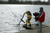Members removing their radio controlled yacht sailing boats after taking part in the Model Yacht Sailing Association, MYSA Round Pond Cup, at The Round Pound, Hyde Park, London. Ten Rater Class of mod... - David Mansell - 2000s,2009,boat,boats,cities,city,club,clubs,communicating,communication,control,controlled,enthusiast,enthusiasts,hobbies,hobby,hobbyist,hobbyists,Leisure,LFL,LIFE,male,man,men,model,models,outdoors,