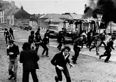 Rioting, The Bogside, Derry, Northern Ireland 1979, prior to the Annual Londonderry Apprentice Boys parade. A bus is highjacked and set on fire as rioting starts by a large group of catholic nationali... - David Mansell - ,1970s,1979,adolescence,adolescent,adolescents,Apprentice,APPRENTICES,apprenticeship,Armed Forces,army,BOY,Boys,British Army,Burning Barricade,Burnt Out,bus,bus service,BUSES,Catholic,catholics,child,