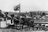 Union Jack Flag flying from a broken lamp post Derry 1979 amongst the ruins of a Protestant street of Victorian terrace houses, due to be demolished and the area redeveloped. Looking towards the River... - David Mansell - &,1970s,1979,Apprentice,APPRENTICES,apprenticeship,belief,BOY,Boys,broken,child,CHILDHOOD,children,conflict,conflicts,conviction,Derry,faith,flag,flags,flying,GOD,houses,Irish,juvenile,juveniles,kid,k