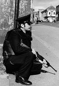 RUC policeman crouched down, gun ready, Falls Road, West Belfast, Northern Ireland 1979 - David Mansell - 04-08-1979