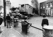 Rioting, Falls Road, West Belfast, Northern Ireland, 1979. Children and a burning HGV chip lorry blocking the road, prior to the Annual Londonderry Apprentice Boys parade - David Mansell - 1970s,1979,adolescence,adolescent,adolescents,Annual Londonderry Apprentice Boys parade,Apprentice,APPRENTICES,apprenticeship,blocking,boy,boys,BURN,burning,Burning Barricade,BURNS,carries,carry,carry