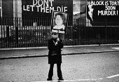 Boy is holding a poster of Bobby Sands, Falls Road, West Belfast, Northern Ireland, 1981. IRA prisoner Bobby Sands started his hunger strike on 1st March and died 66 days later on the 5 May 1981. Ther... - David Mansell - 1980s,1981,catholic,Catholic catholics,cities,city,conflicts conflict,disputes,highway,hunger,hunger strike,imprisonment,incarcerated,incarceration,INMATE,INMATES,IRA,Ireland,Irish,jail,jailed,jails,n