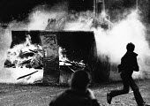 Rioting, Falls Road, West Belfast, Northern Ireland, 1979. Young boys throw stones at an army bulldozer as it clears a burning barricade. The incident happened during the school holidays known as the... - David Mansell - ,1970s,1979,adolescence,adolescent,adolescents,Armed Forces,army,BOY,boys,BURN,burning,Burning Barricade,BURNS,Catholic,catholics,child,CHILDHOOD,children,cities,city,conflict,conflicts,confront,confr