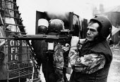Soldier, rioting on the Falls Road, West Belfast, Northern Ireland, 1979. A group of children highjacked the juggernaut lorry in the background and set fire to it. The army have to be very careful of... - David Mansell - 04-08-1979