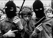 Hooded, armed IRA volunteer gunmen appear infront of the nationalist republican community, Andersontown, West Belfast, 1979 to celebrate the armed struggle for independence of the Dublin Easter Rising... - David Mansell - ,1970s,1979,armed,Armed Forces,arms,Army,assault,assaults,balaclava,balaclavas,carries,carry,carrying,Catholic,catholics,cities,city,communities,community,conflict,conflicts,firearm,firearms,gun,gun.g