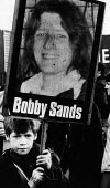 Boy holding a Bobby Sands placard, protest Falls Road, West Belfast. Northern Ireland 1981. Sands, started his hunger strike on 1st March and died 66 days later on the 5 May 1981. There were a total o... - David Mansell - 1980s,1981,activist,activists,against,boy boys,CAMPAIGN,campaigner,campaigners,CAMPAIGNING,CAMPAIGNS,Catholic catholics,child children,cities,city,conflicts conflict,DEMONSTRATING,demonstration,DEMONS
