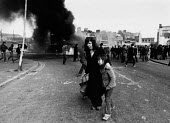 Rioting, The Bogside, Derry, Northern Ireland 1981 after the death of IRA prisoner Bobby Sands on hunger strike. During a lull in rioting a mother and daughter try to find a safe passage, as large num... - David Mansell - 06-04-1981