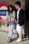A young boy and girl on their Easter school holidays waiting for a tube train on the platform of Harrow on the Hill Tube Station. - David Mansell - ,1st,2010,2010s,adolescence,adolescent,adolescents,adult,adults,boy,boyfriend,BOYFRIENDS,boys,child,CHILDHOOD,children,cities,city,communicating,communication,conversation,conversations,couple,COUPLES