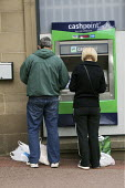 A middle aged couple, a man and women customers using a Lloyds Bank cash dispenser to withdraw cash in Chesterfield in Derbyshire. - David Mansell - 13-06-2009