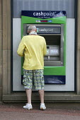 A retired male customer using a Lloyds Bank cash dispenser to withdraw cash in Chesterfield in Derbyshire. - David Mansell - 13-06-2009