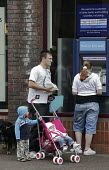 A father and mother and their two young children using a Barclays Bank cash dispenser to withdraw cash in Chesterfield, Derbyshire. - David Mansell - 2000s,2009,ATM,babies,Baby,baby babies,bank,bank banks,banking,banks,bought,boy boys,buy,buyer,buyers,buying,cash,cash machine,cash point,cashmachine,cashpoint,cashpoint cashpoint,child,child children