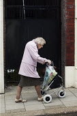 An elderly lady, walking slowly but firmly with the aid of her three wheel mobility trolley in a Chesterfield street, Derbyshire. - David Mansell - 2000s,2009,adult,adults,age,ageing population,bought,buy,buyer,buyers,buying,cities,city,commodities,commodity,consumer,consumers,customer,customers,disabilities,disability,disable,disabled,disablemen