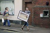 A young married couple, the husband carries a fine art print in a frame, followed by his wife during a saturday afternoon of shopping in the east midlands, market town centre of Chesterfield, Derbyshi... - David Mansell - 13-06-2009