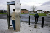 A man using a public telephone box on the 1950s Gurnos council housing estate based on the Radburn system. Merthyr Tydfil has high levels of long term unemployment. It has the highest number of people... - David Mansell - 08-11-2010