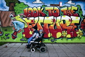 A disable man with a child going past a mural: Look to the Future (by LLOYD ROBERTS), on the shopping centre, on the Gurnos council housing estate which dates from the 1950s, Merthyr Tydfil - David Mansell - 08-11-2010