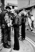 Apprentice boys march, Derry 1978. An apprentice boy talking to British army soldier prior to annual Orange boys appentice march, Protestant enclave The Fountain district, Derry. Londonderry Northern... - David Mansell - 12-08-1978