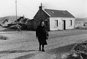 Woman in a traditional black dress crossing the road. Isle of Harris, Outer Hebrides, Scotland - David Mansell - 10-07-1977