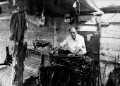 Weaver at work weaving woll in a loom shed making Harris Tweed cloth, Isle of Harris, Outer Hebrides, Scotland. Harris Tweed is hand woven on a treadle loom at each weaver's home. - David Mansell - 1970s,1977,apparel,by hand,clothes,clothing,craft,craftsman,Croft,Crofter,Crofters,Crofting,Crofts,EARNINGS,EBF,Economic,Economy,employee,employees,Employment,EQUALITY,GARMENT,Garment Worker,housing,I