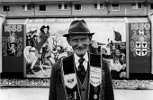 Bobby Jackson, Apprentice boy Past President and mural painter infront of his mural showing King William III crossing the Boyne and the Relief of Deify. Fountain Estate, Londonderry - David Mansell - 12-08-1979