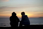 A young couple on holiday watching the sunset, Freshwater West, Pembrokeshire - David Mansell - 05-09-2012