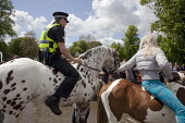 Appleby Horse Fair, Cumbria, Police officer riding a horse bareback supervised by the owner, joining in the spirit of the horse fair - David Mansell - , CLJ,2010s,2015,adolescence,adolescent,adolescents,adult,adults,animal,animals,BAME,BAMEs,bareback,BME,bmes,boy,boys,child,CHILDHOOD,children,CLJ,diversity,domesticated ungulate,domesticated ungulate