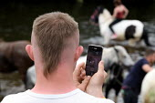 Appleby Horse Fair, Cumbria, a young man who has Down syndrome using his phone camera to record the horses being washed in the River Eden - David Mansell - 2010s,2015,animal,animals,BAME,BAMEs,BME,bmes,communicating,communication,diversity,domesticated ungulate,domesticated ungulates,equestrian,equine,ethnic,ethnicity,Fair,gipsey,Gipsey Gipsy Gypsey,Gips
