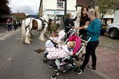 Wickham Horse Fair a traditional one day annual event, Hampshire. Two young mothers from the Travelling community with their beautifully dressed baby girls in prams - David Mansell - 2010s,2015,ACE,adult,adults,animal,animals,babies,baby,BAME,BAMEs,BME,bmes,child,CHILDHOOD,children,communities,community,Culture,diversity,domesticated ungulate,domesticated ungulates,EARLY YEARS,equ