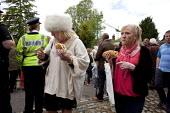 Wickham Horse Fair. Woman eating a hotdog and wearing a very large artificial white fur hat passes an RSPCA inspector. - David Mansell - 2010s,2015,diet,diets,dressed up,eat,eating,fast food,fast food,fastfood,FEMALE,food,FOODS,fur,hat,hats,hotdog,hotdogs,Leisure,LFL,LIFE,Lifestyle,older,PEOPLE,person,persons,RECREATION,RECREATIONAL,RS