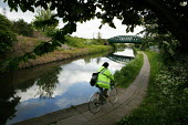 Cycling to work along the towpath of The Grand Union Canal, a Railway bridge crosses the canal. Willesden London - David Mansell - 09-05-2005