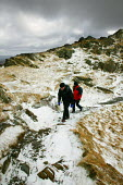 Two walkers, man and woman carrying their day backpacks walking along the route to climb Cader Idris mountain, 892 metres high, situated in the Snowdonia National Park, North Wales. - David Mansell - 12-03-2005