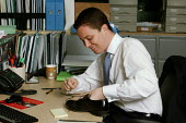City office workers at work in their offices at CB Richard Ellis, the world's largest property estate agents based in the square mile of the City of London. A young man is putting new laces into his p... - David Mansell - 09-04-2006