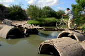 A rickety bridge over a polluted canal in a barrio where maquiladora workers and their families live in Matamoros. The neighborhoods are contaminated by toxic chemicals dumped by factories into the ca... - David Bacon - 05-11-2006