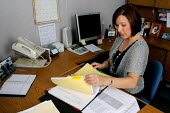 A school office worker in Anaheim, CA. - David Bacon - ,2000s,2006,administrator,administrators,America,assistant,assistants,busy,clerical,clerk,clerks,desk,desks,EARNINGS,edu education,EQUALITY,female,file,files,filing,Income,INCOMES,inequality,LAB LBR W