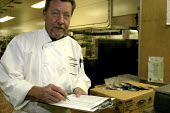 A cook at the St. Francis Hotel, one of the most luxurious hotels in the USA, San Francisco - David Bacon - ,2000s,2007,America,BAME,BAMEs,BME,bmes,box,boxes,can,cans,check,checking,chef,chefs,clipboard,clipboards,cook,cooks,deliveries,DELIVERING,delivery,Diaspora,diversity,EBF,Economic,Economy,ethnic,ethni