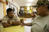 Frank Curiel, an organiser for the Laborers International Union and the Mississippi Immigrant Rights Alliance, talks with Samuel Holguin, owner of the La Veracruzana market. Laurel, Mississippi is a t... - David Bacon - 14-01-2008