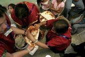 Indigenous Triqui women prepare meat and their traditional large tortillas.The assembly of the Indigenous Front of Binational Organizations in Mixteca region of Oaxaca, one of the poorest areas in Mex... - David Bacon - 31-05-2008
