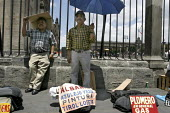 Jornaleros or day laborers in construction, wait for someone to hire them at the side of the Cathedral in Mexico Citys main plaza, the Zocalo. One advertises his skill as albanil, or mason, while anot... - David Bacon - ,2000s,2008,americas,Amerindian,Amerindians,BUILDING,BUILDINGS,casual,Cathedral,CATHEDRALS,construction,Construction Industry,for,hire,jobless,jobseeker,jobseekers,LAB LBR Work,Latin America,male,man,