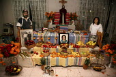 Artist Alejandro Vera and his wife in front of a altar they have made for Day of the Dead. - David Bacon - 04-11-2008