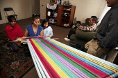 Santa Paula, California. The family of Miguel Alonso are Purepecha migrants from Turicuaro in the Mexican state of Michoacan. Consuelo Alonso shows her two daughters how she weaves a multi-colored reb... - David Bacon - 24-04-2009