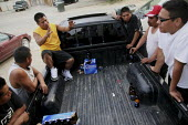 Alberto Garcia talks with other men as they drink beer, discuss work and relax around a pickup truck after work. A community of a few hundred migrant indigenous Mixtec farmworkers from Oaxaca live in... - David Bacon - 11-06-2009