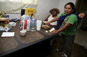 Juse Guadalupe Silva, Soledad Lopez and their baby Mariflor Silva eat dinners together after coming home from work. A community of a few hundred migrant indigenous Mixtec farmworkers from Oaxaca live... - David Bacon - 11-06-2009