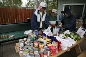 Day laborers bag and distribute donated food parcels to workers who don't have enough to eat, Graton Day Labor Center, Sonoma County, California, Most are migrants from Oaxaca. The center was built wi... - David Bacon - 21-07-2009