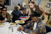 A volunteer serves food to seniors at St. Mary's. Poor elderly eat lunch at St. Mary's Center in Oakland, California, which provides food for poor people. Food for the program comes from the Alameda C... - David Bacon - &, American,2000s,2009,adult,adults,African American,African Americans,age,aged,ageing population,aid,America,American,americans,assistance,BAME,BAMEs,belief,black,BME,bmes,BREAK,California,Catholic,c