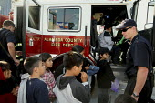 USA Firefighters give the children of food recipients a chance to sit in their fire engine whilst their families are waiting for food. The poor receive bags and shopping carts of food and food parcels... - David Bacon - 15-08-2009