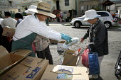 Good Samaritan Food Pantry distributing food to Oakland residents on the sidewalk in front of a house where food is stored and bagged. Before the distribution starts, dozens of people, many of them Ch... - David Bacon - 28-08-2009