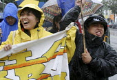 Hundreds of workers rally and march through the streets of Oakland California in the rain to celebrate May Day and demand rights and legal status for immigrants. - David Bacon - 2000s,2009,activist,activists,America,asian,asians,BAME,BAMEs,banner,banners,BME,bmes,California,CAMPAIGN,campaigner,campaigners,CAMPAIGNING,CAMPAIGNS,DEMONSTRATING,demonstration,demonstration America