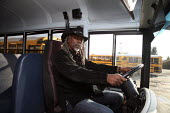 A school bus driver for the Sequoia Union High School District at the wheel of his bus. California - David Bacon - 2000s,2009,African American,African Americans,America,and,BAME,BAMEs,black,BME,BME Black minority ethnic American,bmes,bus,bus service,buses,California,cities,city,County,cowboy,diversity,dreadlocks,d