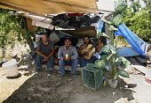 Three immigrant Mexican farm workers share a small camp under the trees. They have only been able to work a few days in the last few months, and cannot afford accommodation. They call it living sin te... - David Bacon - 2010,2010s,accommodation,agricultural,agriculture,America,American,americans,asleep,BAME,BAMEs,BME,bmes,camp,camping,camps,capitalism,capitalist,casual workers,destitute,Diaspora,diversity,EARNINGS,em