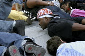 """A rally protesting at the killing of Oscar Grant, a young African American, by an officer of the Bay Area Rapid Transit police. Protesters lie on the ground, and shout out """"Don't Shoot!"""" to remind onl... - David Bacon - , American,2000s,2009,activist,activists,adult,adults,African,African American,African Americans,America,American,americans,BAME,BAMEs,black,BME,bmes,CAMPAIGN,campaigner,campaigners,CAMPAIGNING,CAMPAI"""